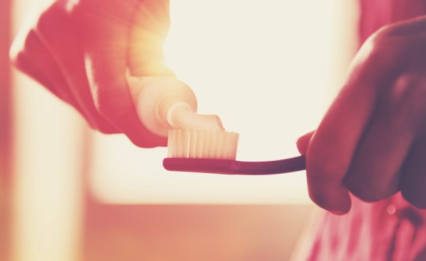 Hands holding a toothbrush and placing toothpaste on it in morning sunrise