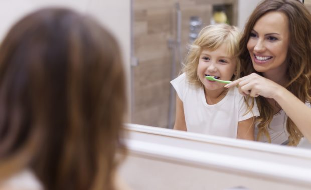 Morning lesson of brushing teeth with mommy